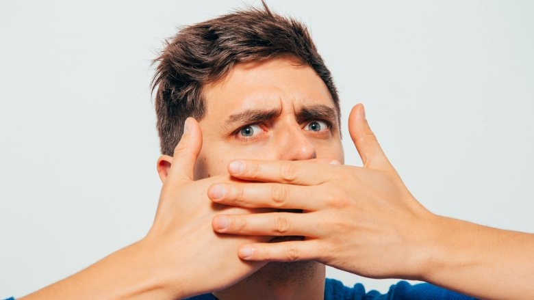 Man covering mouth