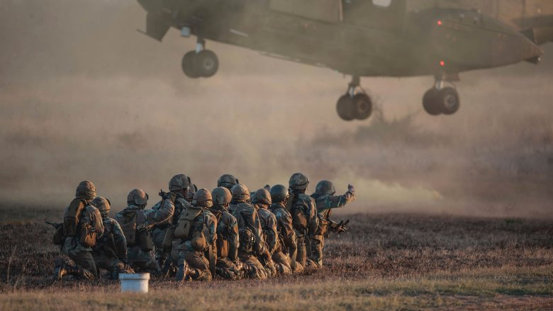 military soliders crouching helicopter