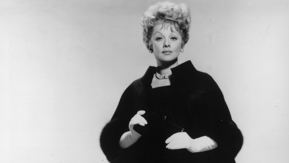 Lucille Ball wearing black coat and white gloves