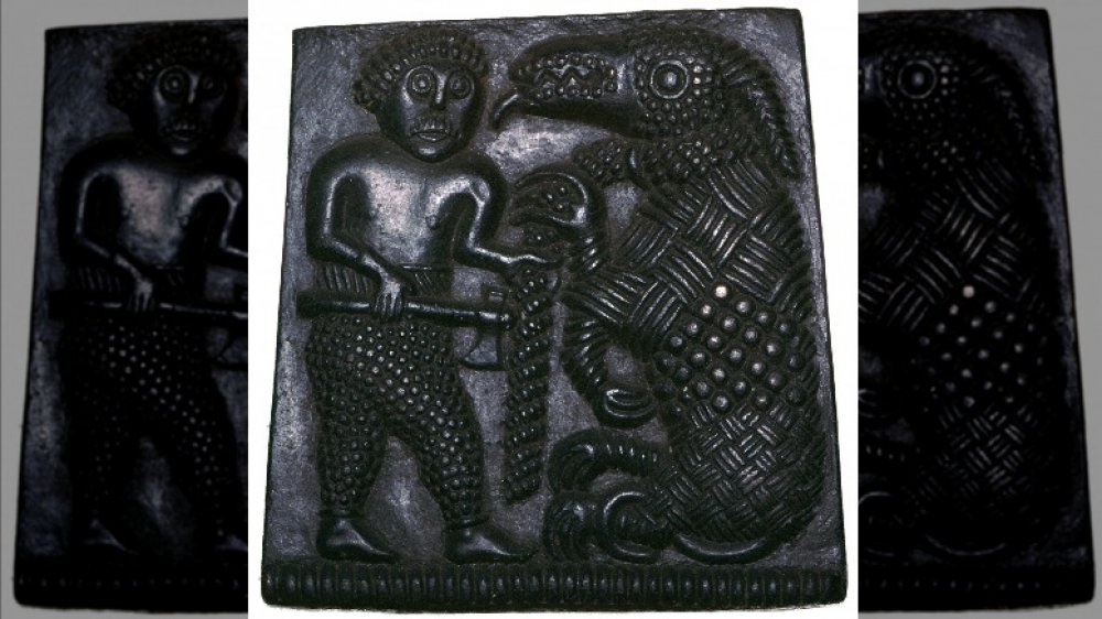 Bronze plaque showing a Viking holding a chained bear