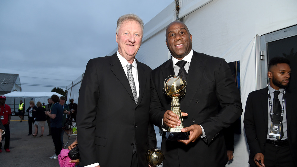 Magic Johnson and Larry Bird standing and smiling