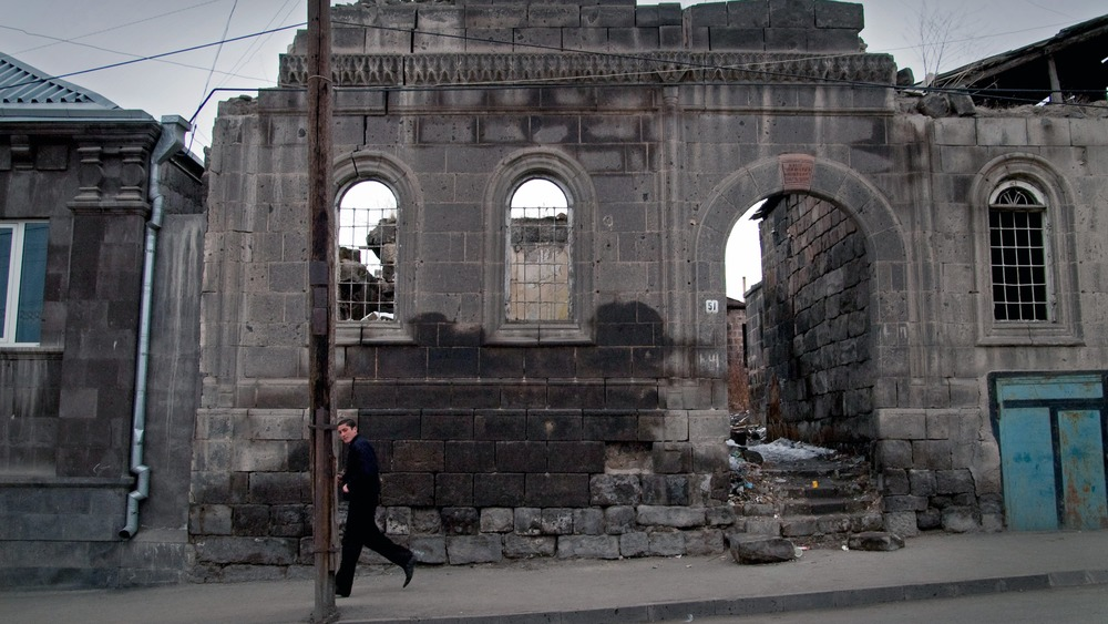 Gyumri resident walks by a building destroyed by the 1988 Earthquake on March 21, 2005